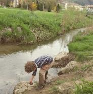 Enfant jouant au bord d'un ruisseau